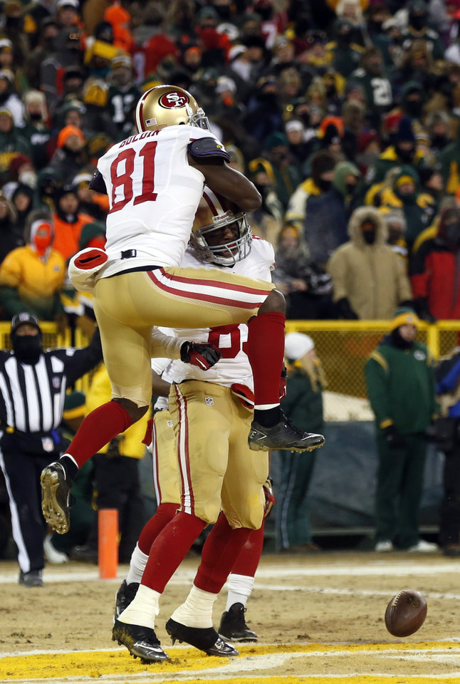 Photo - San Francisco 49ers wide receiver Anquan Boldin (81) jumps on tight end Vernon Davis (85) after Davis makes a touchdown catch during the second half of an NFL wild-card playoff football game against the Green Bay Packers, Sunday, Jan. 5, 2014, in Green Bay, Wis. (AP Photo/Jeffrey Phelps)