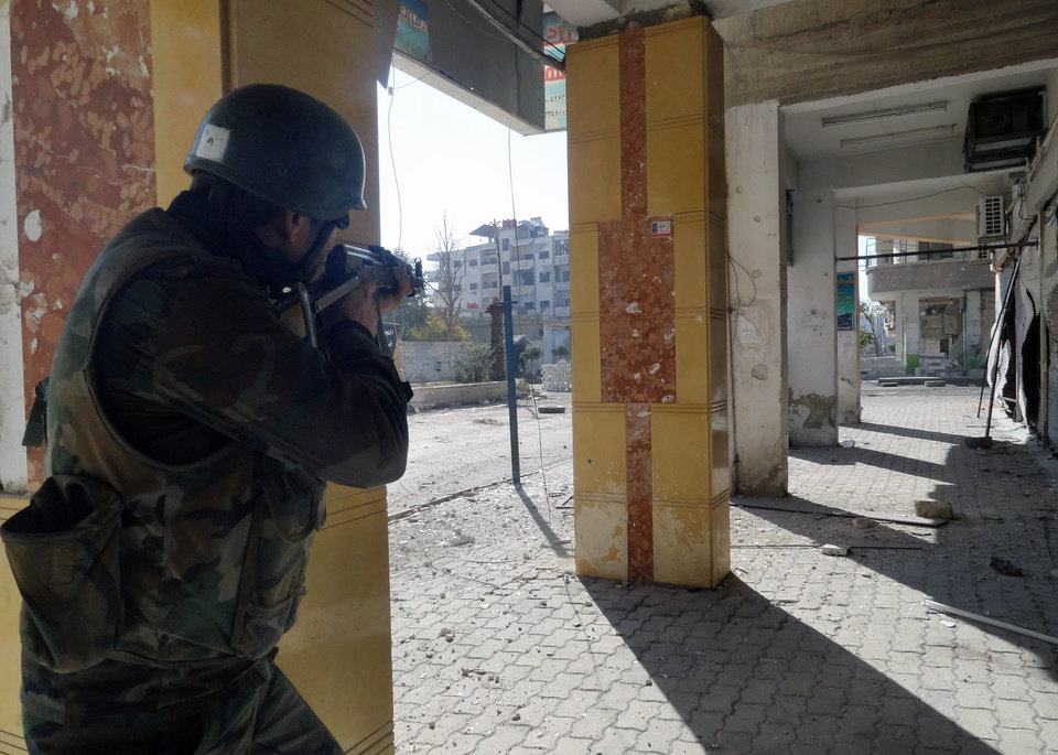 Photo - In this Sunday, Dec. 2, 2012 photo released by the Syrian official news agency SANA, a Syrian soldier aims his rifle at free Syrian Army fighters during clashes in the Damascus suburb of Daraya, Syria. Syrian warplanes and artillery pummeled areas in and around Damascus, Aleppo and several other cities, on Sunday according to reports received by human rights activists. Intense fighting persists as rebels try to push their way back into the capital, where President Bashar Assad has his power base. (AP Photo/SANA)