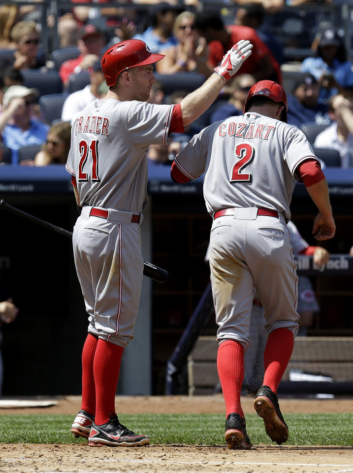 Photo - Cincinnati Reds' Zack Cozart, right, celebrates with Todd Frazier after scoring during the fifth inning of a baseball game against the New York Yankees at Yankee Stadium, Sunday, July 20, 2014, in New York. (AP Photo/Seth Wenig)