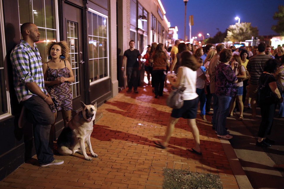 Photo - David and Amanda Similly take a break at the side with their dog Timber during H&8th on Hudson between 7th and 8th streets, Friday, September 27, 2013. Photo by Doug Hoke, The Oklahoman