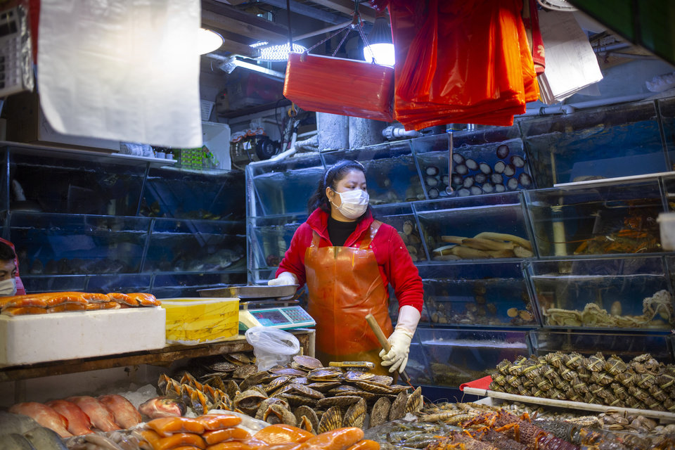 Photo -  An employee wears a face mask as she works at a seafood stall at a market in Beijing, Saturday, March 14, 2020. The United States declared a state of emergency Friday as many European countries went on a war footing amid mounting deaths as the world mobilized to fight the widening coronavirus pandemic. For most people, the new coronavirus causes only mild or moderate symptoms, such as fever and cough. For some, especially older adults and people with existing health problems, it can cause more severe illness, including pneumonia. (AP Photo/Mark Schiefelbein)