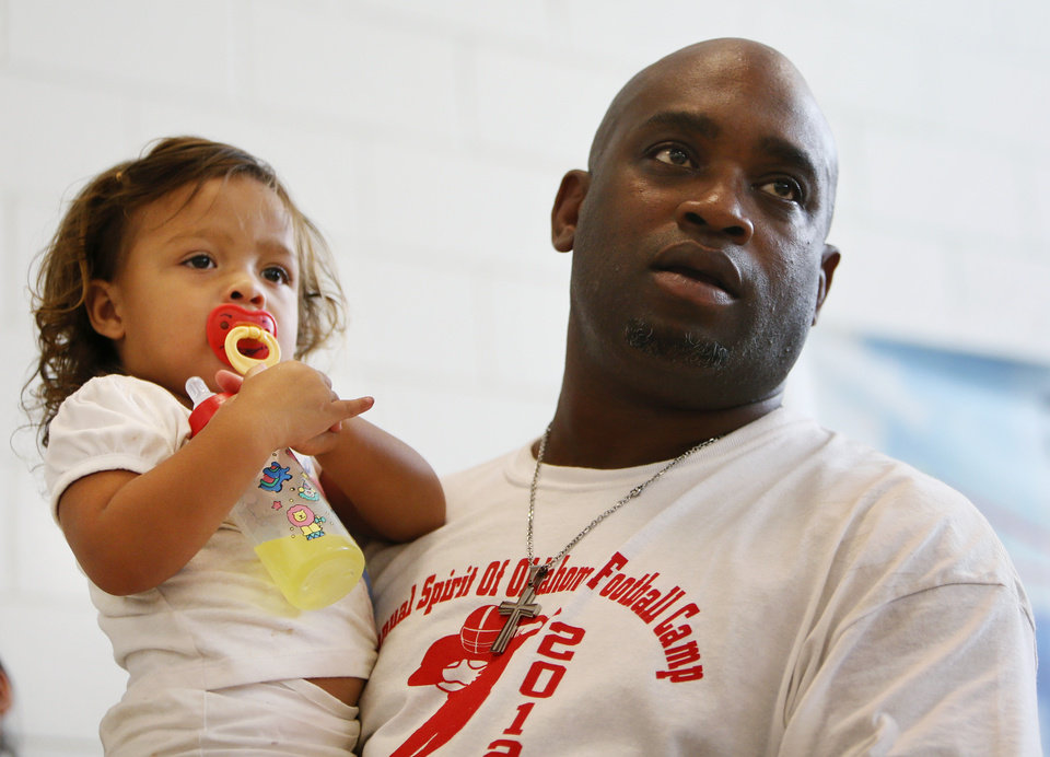 Photo - Former OU quarterback Jamelle Holieway holds daughter Jasmin Holieway, 2, as he talks to campers during Holieway's Spirit of Oklahoma football camp in Weleetka, Okla., Friday, July 6, 2012. Photo by Nate Billings, The Oklahoman