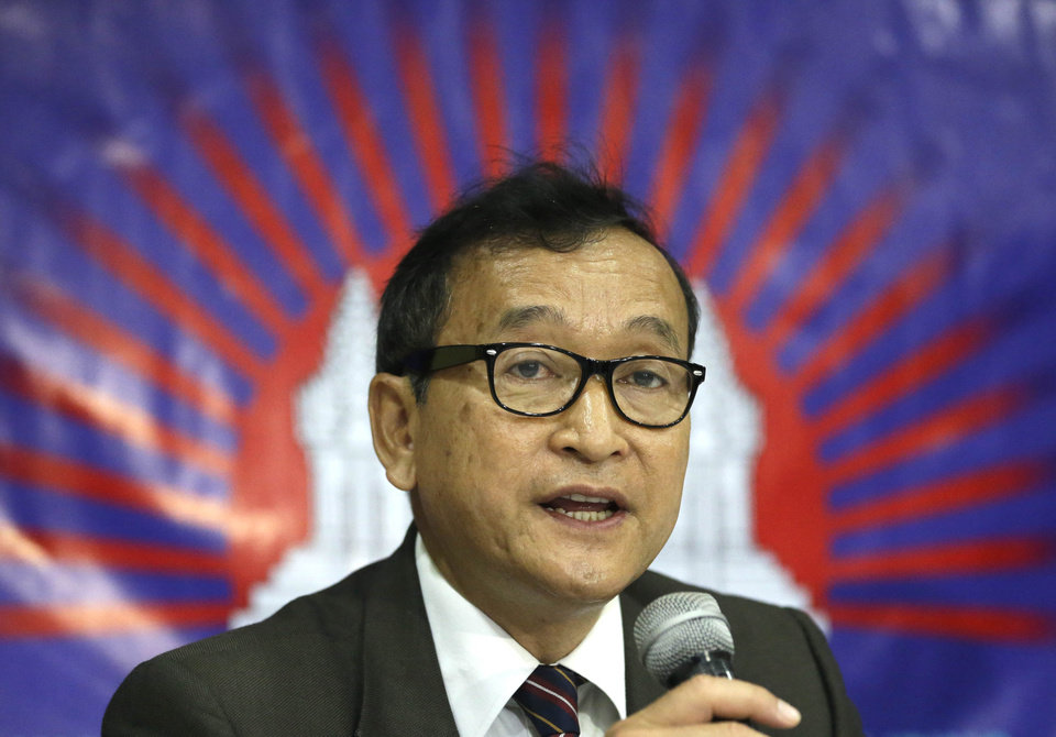 FILE - In this Sept. 10, 2012 file photo, Cambodian opposition leader Sam Rainsy, who was currently living in exile in France, talks about the opposition\'s plans for 2013 elections in Cambodia during the launching of the International Parliamentary Committee for Democratic Elections in Cambodia with Philippine Sen. Franklin Drilon in San Juan, east of Manila, Philippines. Thousands of cheering supporters greeted Cambodian opposition leader Sam Rainsy as he returned from self-imposed exile Friday, July 19, 2013 to spearhead his party\'s election campaign against well-entrenched Prime Minister Hun Sen. (AP Photo/Bullit Marquez, File)