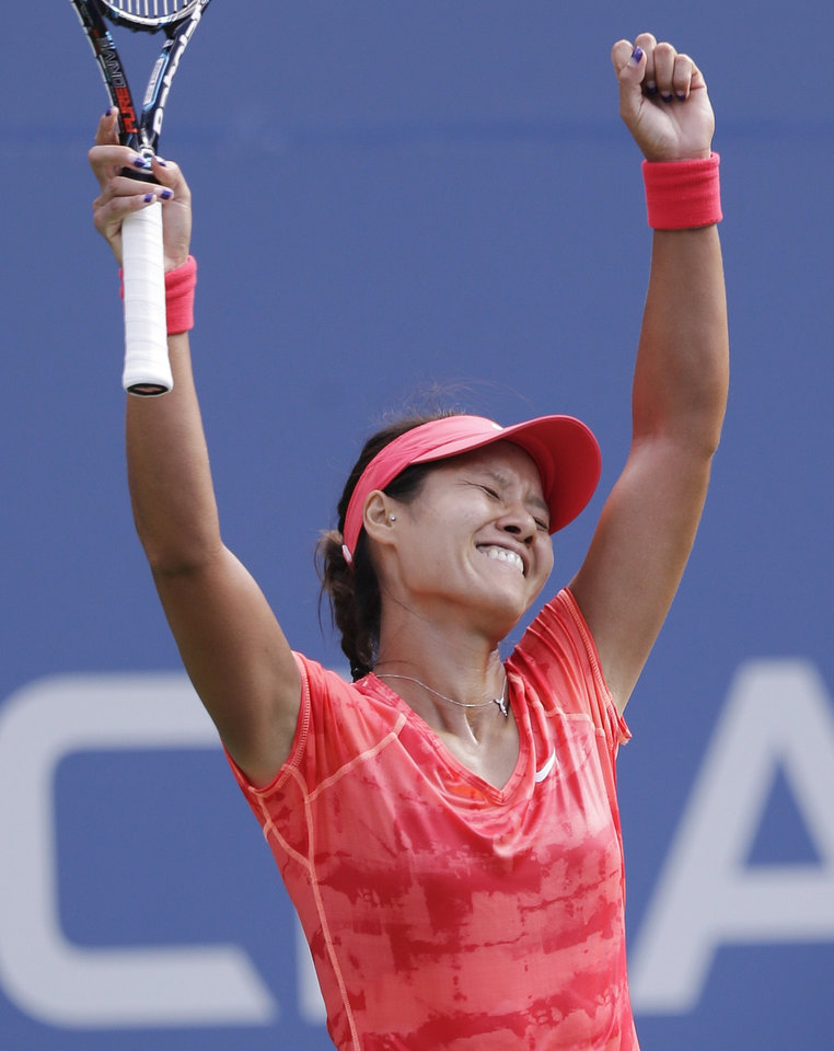 Photo - Li Na, of China, reacts after beating Ekaterina Makarova, of Russia, during the quarterfinals of the 2013 U.S. Open tennis tournament, Tuesday, Sept. 3, 2013, in New York. (AP Photo/Julio Cortez)