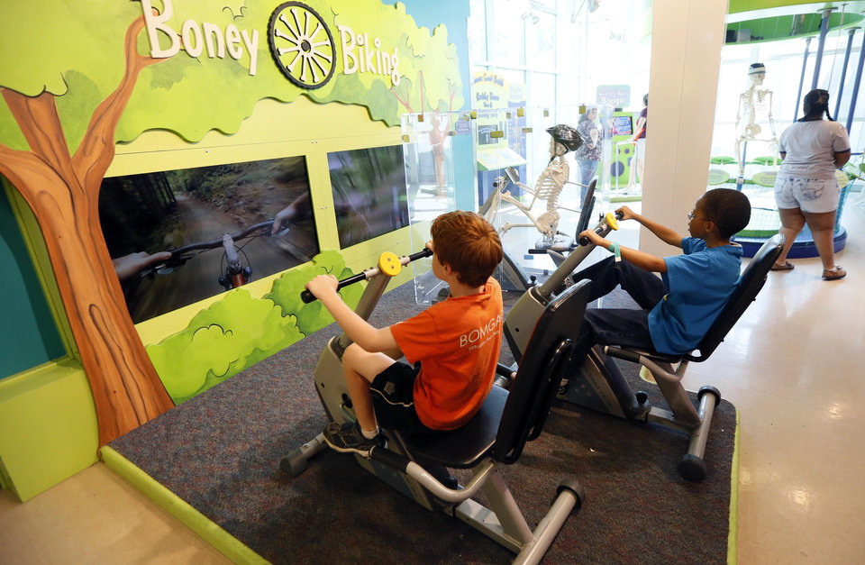 Photo - In this July 3, 2014 photograph, children race a skeletal bike racer at an interactive exercise station at the Mississippi Children's Museum in Jackson, Miss. The interactive hands-on facility promotes literacy, health and nutrition, learning the state's heritage and exploration of its cultural arts and key economic industries in a fun setting. (AP Photo/Rogelio V. Solis)