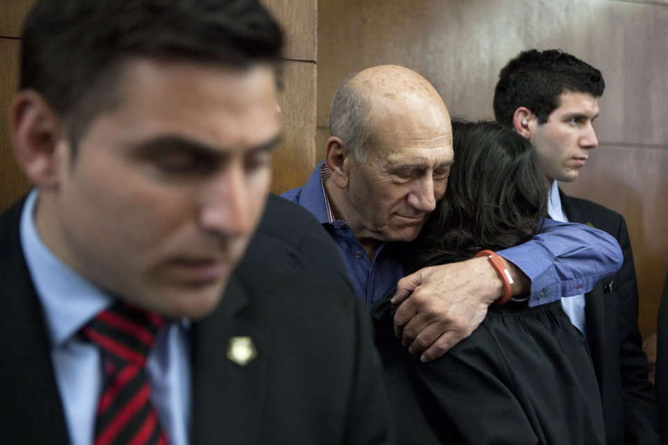 Photo - Former Israeli Prime Minister Ehud Olmert hugs a friend before a hearing at Tel Aviv's District Court. Monday, March 31, 2014. The court handed down the verdict in the wide-ranging Jerusalem real estate scandal case related to Olmert's activities before becoming prime minister in 2006. A total of 13 government officials, developers and other businesspeople were charged in three separate schemes. (AP Photo/Dan Balilty, Pool)
