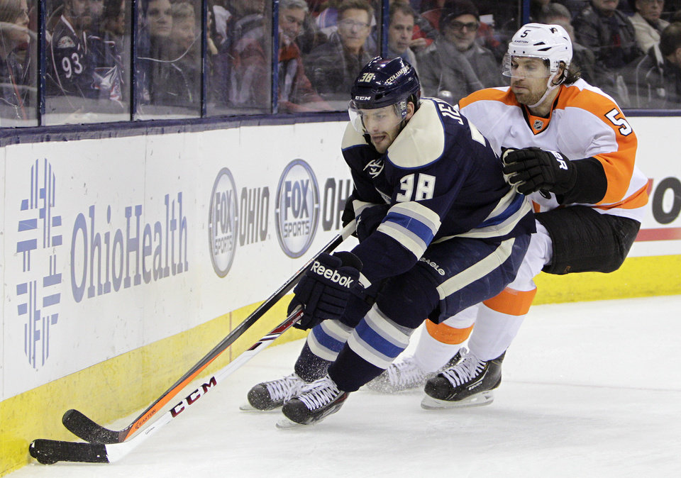 Photo - Columbus Blue Jackets' Boone Jenner, left, carries the puck as Philadelphia Flyers' Braydon Coburn defends during the second period of an NHL hockey game Thursday, Jan. 23, 2014, in Columbus, Ohio. (AP Photo/Jay LaPrete)