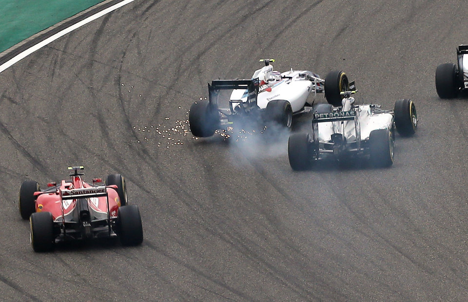 Photo - Williams driver Felipe Massa of Brazil, center left, and Mercedes driver Nico Rosberg of Germany, right, collide into turn one at the start of the Chinese Formula One Grand Prix at Shanghai International Circuit in Shanghai, Sunday, April 20, 2014. (AP Photo/Eugene Hoshiko)