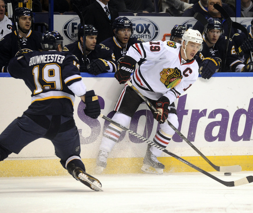 Chicago Blackhawks' Jonathan Toews, right, looks to pass around St. Louis Blues' Jay Bouwmeester during the first period of an NHL hockey game Saturday, Dec. 28, 2013, in St. Louis. (AP Photo/Bill Boyce)