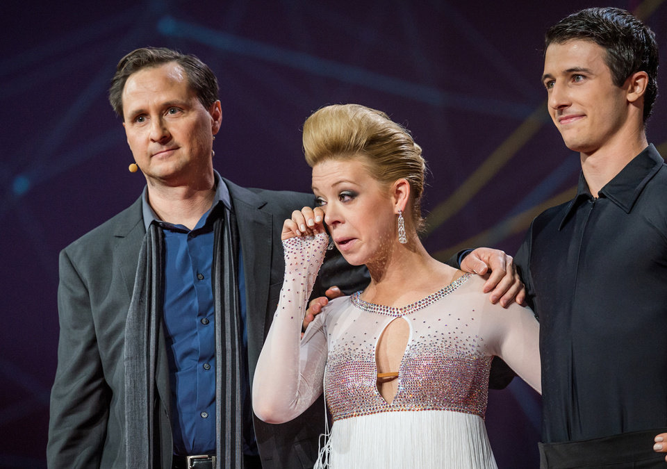 Photo - In this photo provided by TED 2014 Conference, dancer Adrianne Haslet-Davis, center, wipes away a tear while standing on stage with MIT professor Hugh Herr, left, and dancer Christian Lightner, at the 2014 TED Conference, Wednesday, March 19, 2014, in Vancouver, British Columbia. Haslet-Davis took to the stage to perform for the first time since losing part of her left leg in the 2013 Boston Marathon bombing. Herr designed the bionic leg specifically for dancing after visiting Haslet-Davis in the hospital. (AP Photo/TED 2014 Conference, James Duncan Davidson)
