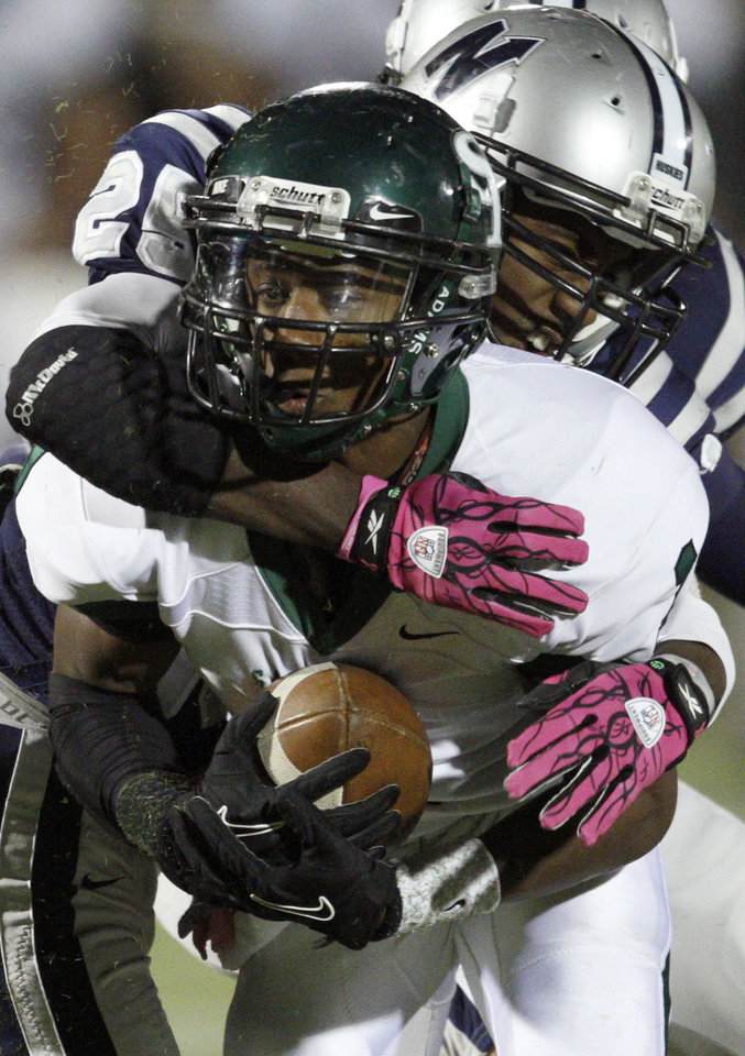 Edmond Santa Fe's Patrick Hinton is brought down by Edmond North's Christian Peterson during a high school football game at Wantland Stadium in Edmond, Okla., Friday, Oct. 29, 2010.  Photo by Bryan Terry, The Oklahoman