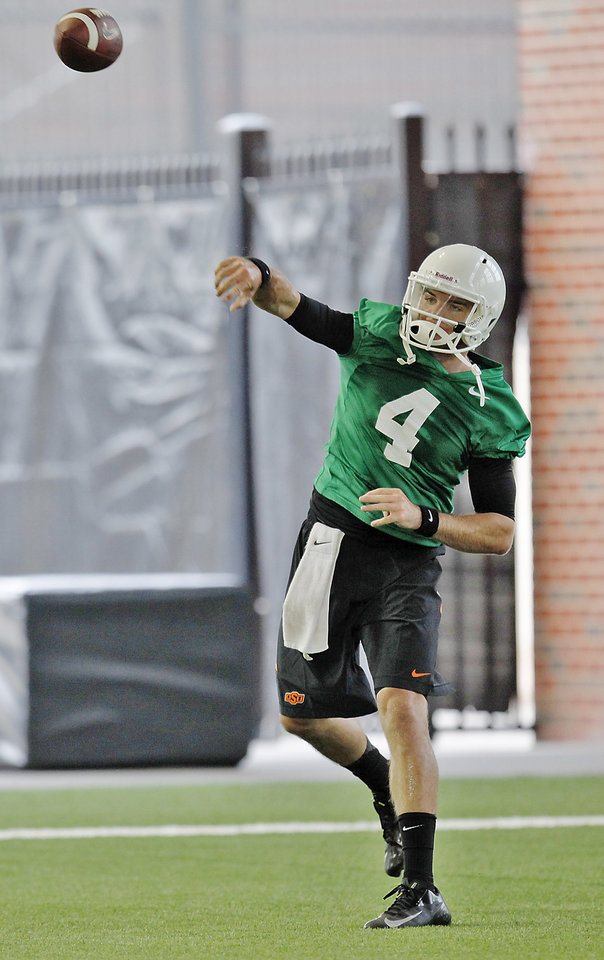 Photo - Oklahoma State quarterback J.W. Walsh (4) throws the ball during the first team practice of the fall at the Sherman E. Smith Training Facility on the campus of Oklahoma State University in Stillwater on August 1, 2014. Photo by KT King, The Oklahoman