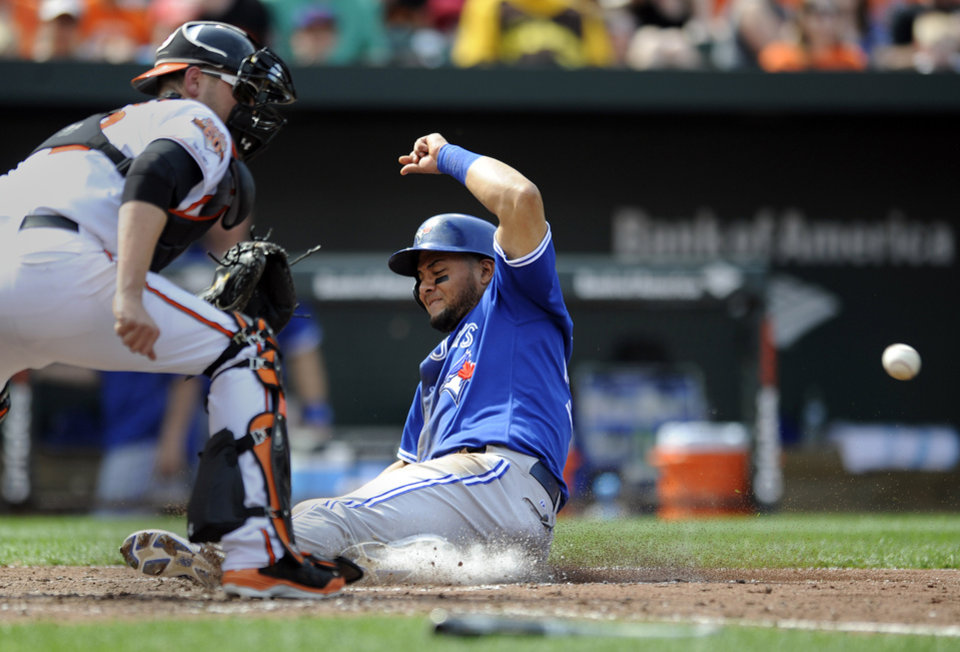 Photo - Toronto Blue Jays' Melky Cabrera, right, slides safely across home plate on a single hit by Colby Rasmus as Baltimore Orioles catcher Matt Wieters awaits the throw in the sixth inning of a baseball game on Sunday, April 13, 2014, in Baltimore. (AP Photo/Gail Burton)