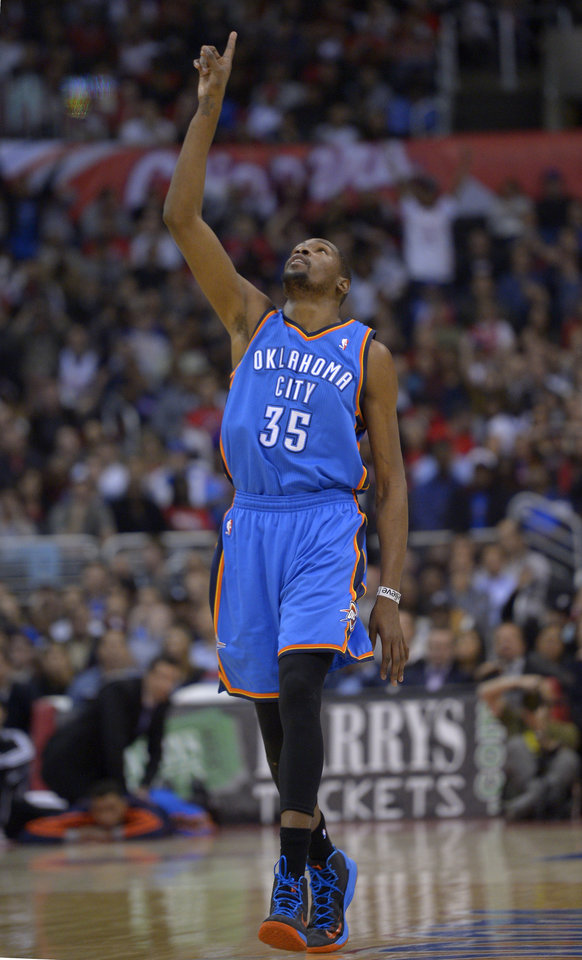 Oklahoma City Thunder forward Kevin Durant points to the sky after hitting a three point shot during the second half of their NBA basketball game against the Los Angeles Clippers, Tuesday, Jan. 22, 2013, in Los Angeles. The Thunder won 109-97.  (AP Photo/Mark J. Terrill)  ORG XMIT: LAS106