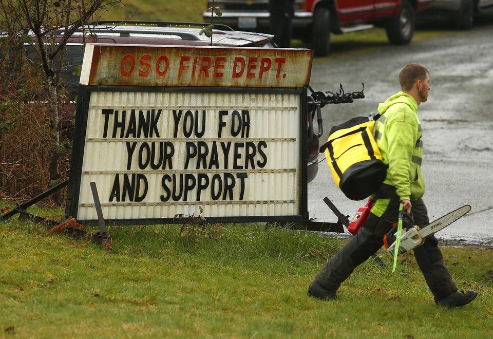 Photo - Volunteers arrive at the Oso Fire Department, Tuesday, March 25, 2014, in Oso, Wash. A massive mudslide struck near Arlington, Wash., on Saturday. At least 14 people were killed over the weekend and scores more missing. (AP Photo/The Herald, Mark Mulligan)