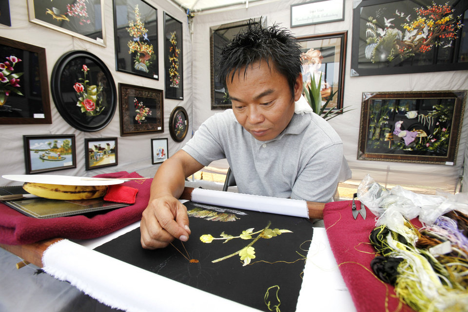 Photo - Silk embroidery artist Don Tran works on a piece inside his booth during the Paseo Arts Festival in Oklahoma City, OK, Saturday, May 26, 2012,  By Paul Hellstern, The Oklahoman
