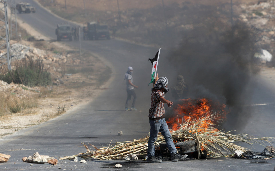 Photo - Palestinian protesters face Israeli soldiers during clashes, following a protest against the Israeli military action in Gaza, in the West Bank city of Nablus on Friday, Aug. 22, 2014. (AP Photo/Nasser Ishtayeh)