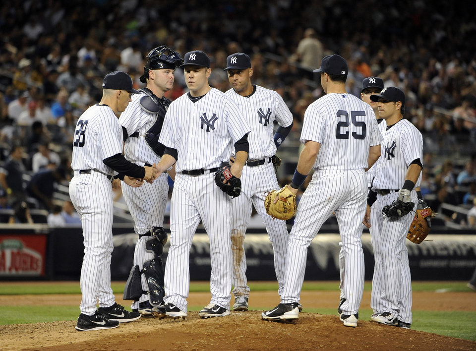 Photo - New York Yankees manager Joe Girardi (28) takes starting pitcher David Phelps (41) out of the interleague baseball game against the Cincinnati Reds in the seventh inning at Yankee Stadium on Friday, July 18, 2014, in New York. (AP Photo/Kathy Kmonicek)