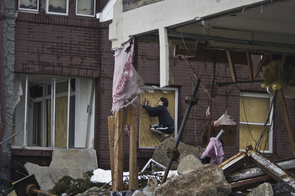 Marcus Konner, 22, boards his home in the aftermath of a storm surge from Hurricane Sandy, Tuesday, Oct. 30, 2012, in Coney Island's Sea Gate community in New York.  (AP Photo/Bebeto Matthews) ORG XMIT: NYBM113