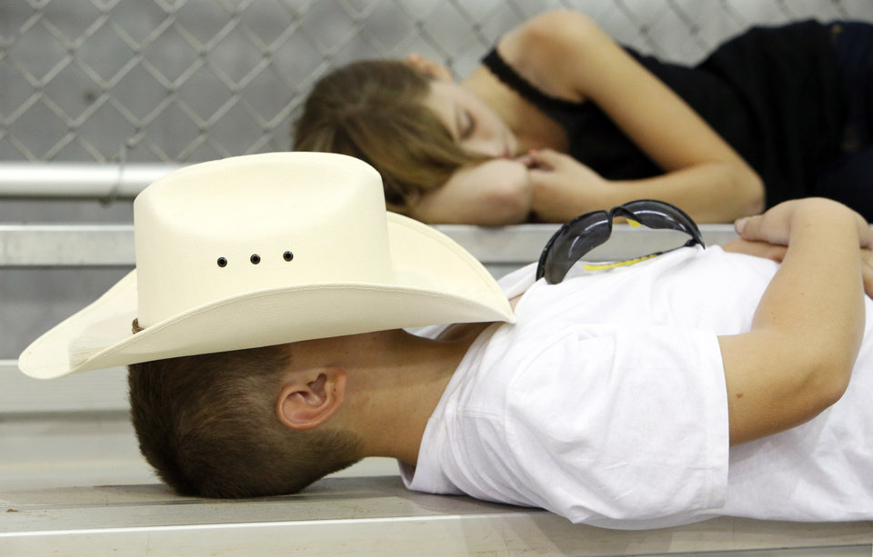 Harley Milliken, 8, of Vacaville, Calif., takes a nap with his hat over his face next to sister Makayla Milliken, 11,  during the National Finals for the Ranch Sorting National Championships, part of the Battle in the Saddle, at the State Fair Park in Oklahoma City, Thursday, July 5, 2012. Photo by Nate Billings, The Oklahoman