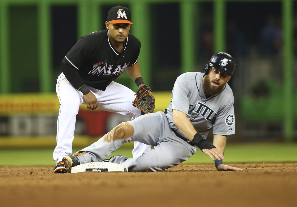 Photo - After tagging out Seattle Mariners' Dustin Ackley, right, Miami Marlins' Donovan Solano waits to if he got a double play during the sixth inning of a baseball game in Miami, Saturday, April 19, 2014. Solano got the double play. (AP Photo/J Pat Carter)