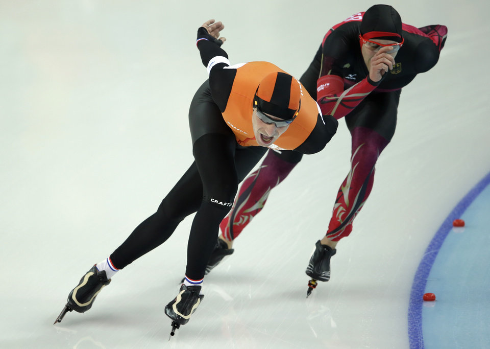 Photo - Bob de Jong of the Netherlands laps Alexej Baumgaertner of Germany in the penultimate lap during the men's 10,000-meter speedskating race at the Adler Arena Skating Center during the 2014 Winter Olympics in Sochi, Russia, Tuesday, Feb. 18, 2014. (AP Photo/Patrick Semansky)