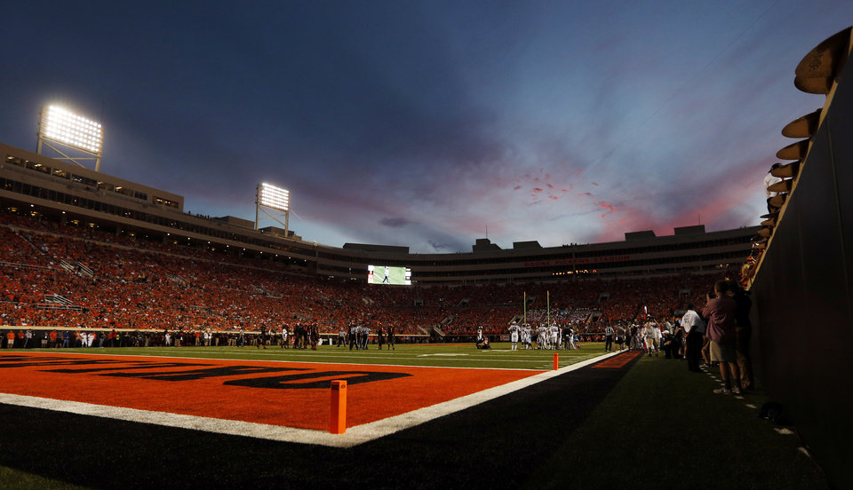 Photo - The sun sets behind Boone Pickens Stadium during a college football game between the Oklahoma State Cowboys (OSU) and the Texas Tech Red Raiders at Boone Pickens Stadium in Stillwater, Okla., Thursday, Sept. 25, 2014. Photo by Nate Billings, The Oklahoman
