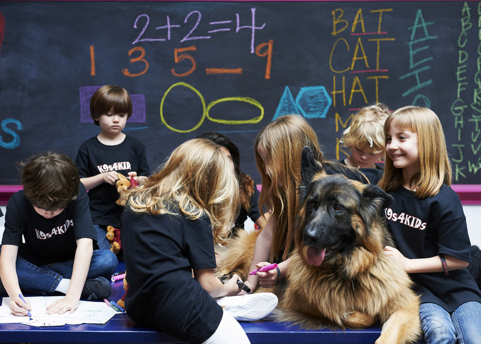 Photo - In this Feb. 18, 2013 photo provided by K9s4KIDS, children share time with canine mascot Johnny Cash at the TutorVille HUB in Houston.  Schools have beefed up security, staged mock drills and added metal detectors, cameras and alarms to prevent violence. Some think teachers should be armed and the National Rifle Association wants armed police in every American school.  Kristi Schiller thinks some special dogs might do the trick. She wants her charity, K9s4KIDS, to do for schools what it's done for police departments in the U.S. - place scores of trained dogs among their ranks through the nonprofit set up in 2009. (AP Photo/K9s4KIDS, Josh Welch)