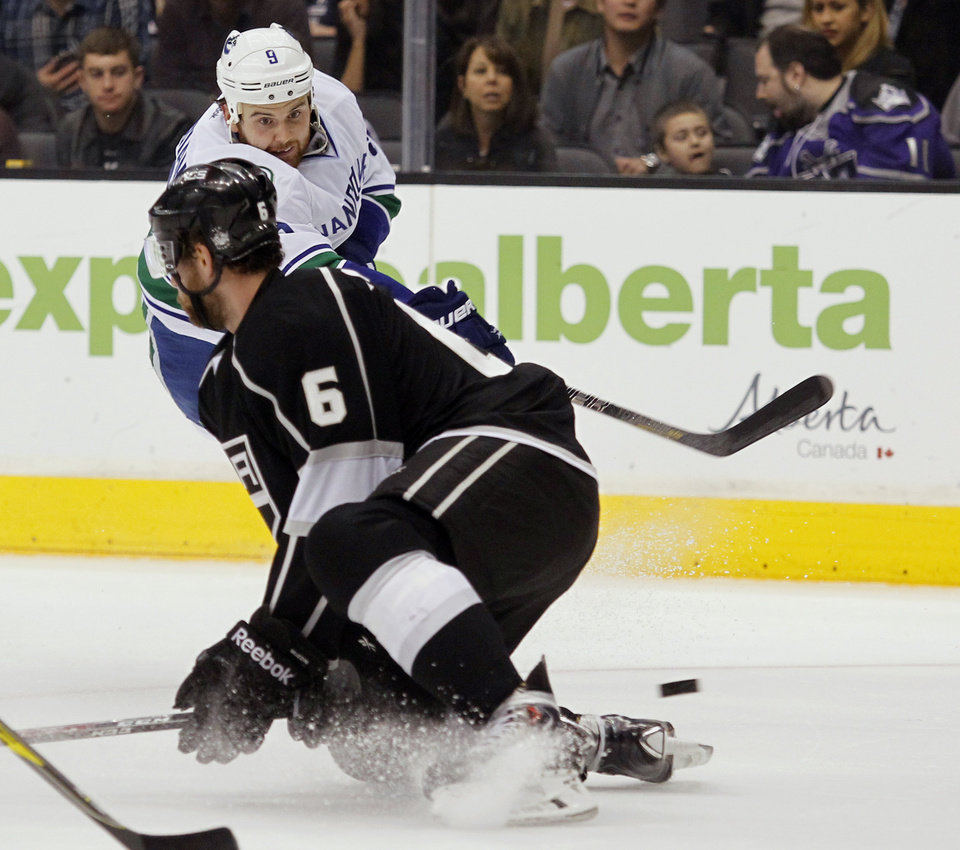 Photo - Vancouver Canucks right wing Zack Kassian (9) shoots the puck in front of Los Angeles Kings defenseman Jake Muzzin (6) during the first period of an NHL hockey game on Saturday, Jan. 4, 2014, in Los Angeles. (AP Photo/Alex Gallardo)