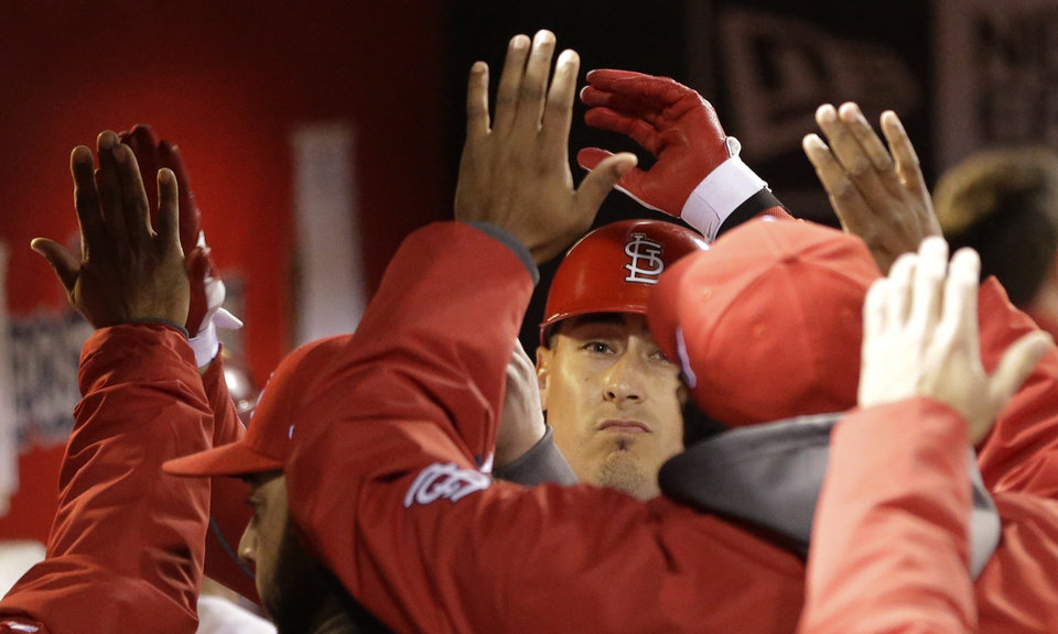 Photo -   St. Louis Cardinals' Allen Craig is congratulated after his sacrifice fly ball to score Matt Carpenter from third during the first inning of Game 4 of baseball's National League championship series against the San Francisco Giants Thursday, Oct. 18, 2012, in St. Louis. (AP Photo/David J. Phillip)
