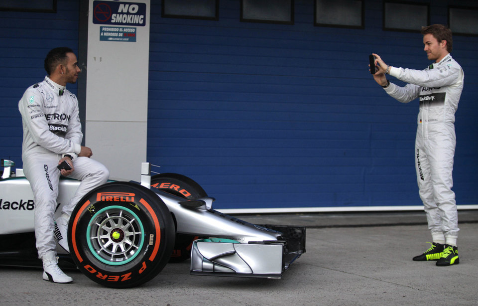 Photo - Mercedes GP drivers Nico Rosberg of Germany, right, takes photographs on his smertphone camera of Lewis Hamilton of Great Britain, left, during the launch of their new Mercedes W05 Formula One car at the Circuito de Jerez on Tuesday, Jan. 28, 2014, in Jerez de la Frontera, Spain. (AP Photo/Miguel Angel Morenatti)