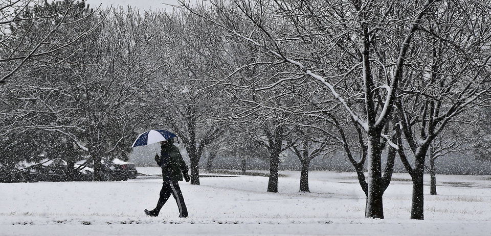 A pedestrian carries an umbrella while walking through the heavy snow fall in downtown Oklahoma City on Tuesday, Feb.12, 2013, in Oklahoma City, Okla. Photo by Chris Landsberger, The Oklahoman