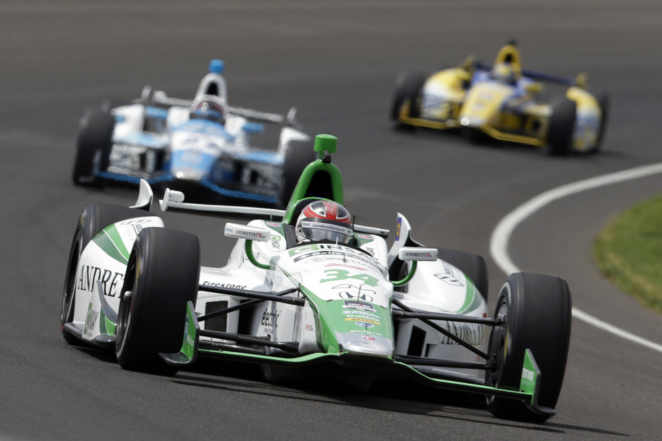 Photo - Carlos Munoz, of Colombia, leads E. J. Viso, of Venezuela, center, and Marco Andretti though the first turn during practice for Indianapolis 500 IndyCar auto race at the Indianapolis Motor Speedway in Indianapolis, Monday, May 12, 2014. (AP Photo)