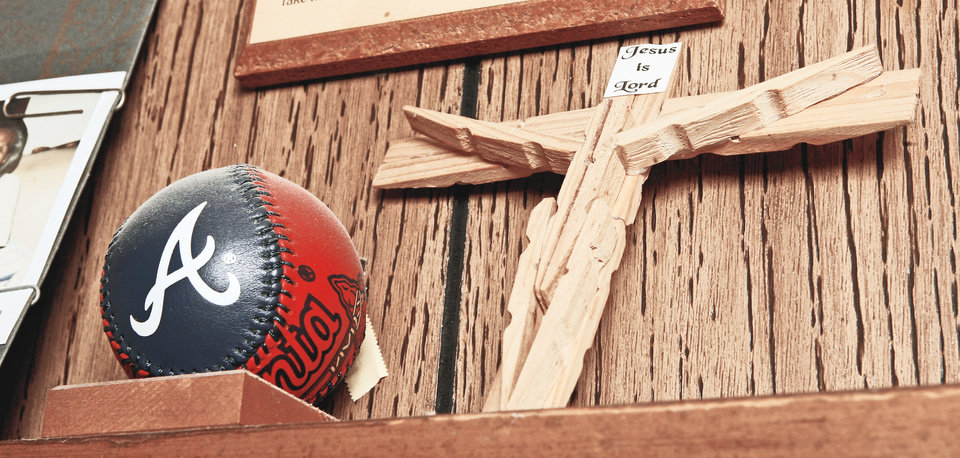A Braves baseball and a cross are on display on a shelf in the bedroom of Oklahoma City resident Robert Jones. Baseball and his faith are things he says he holds dear. PHOTO BY PAUL B. SOUTHERLAND, THE OKLAHOMAN