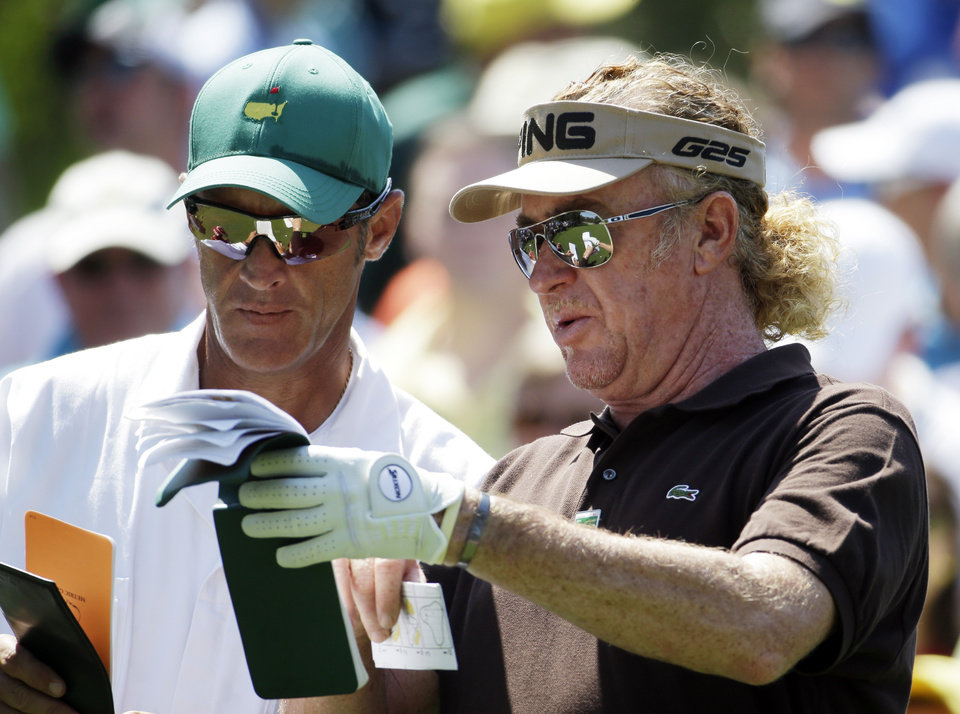 Photo - Miguel Angel Jimenez, of Spain, checks his notebook with caddie Clifford Botha before teeing off on the sixth hole during the third round of the Masters golf tournament Saturday, April 12, 2014, in Augusta, Ga. (AP Photo/Darron Cummings)