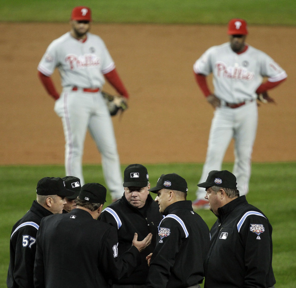 Photo - FILE - In this Oct. 28, 2009, file photo, Philadelphia Phillies' Pedro Feliz, left, and Jimmy Rollins watch in the background, as umpires discuss a call at first base during the fifth inning in Game 1 of the baseball's World Series against the New York Yankees in New York. Major League Baseball announced Thursday, Jan. 16, 2014, that it will greatly expand instant replay to review close calls starting this season. Each manager will be allowed to challenge at least one call per game. If he's right, he gets another challenge.  After the seventh inning, a crew chief can request a review on his own.  (AP Photo/Julie Jacobson, File)