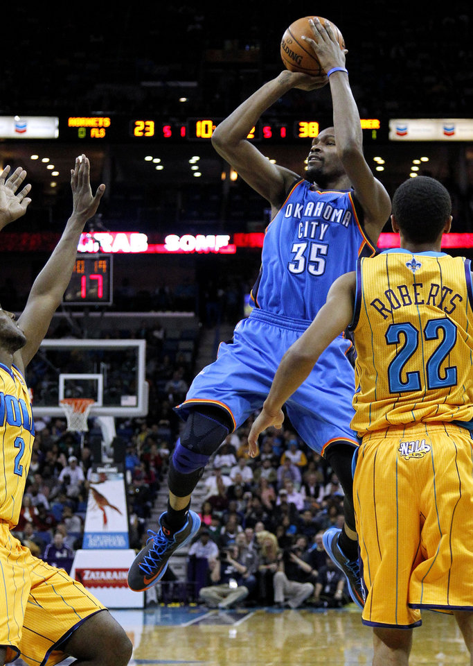 Photo - Oklahoma City's Kevin Durant (35) shoots the ball over New Orleans Hornets Darius Miller (2) and Brian Roberts (22) during the first half of an NBA basketball game in New Orleans, Friday, Nov. 16, 2012. (AP Photo/Jonathan Bachman) ORG XMIT: LAJB103