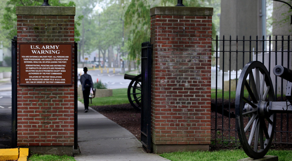 Photo -   A person walks towards the security gate at Fort Hamilton, in the Brooklyn borough of New York, check vehicles as they enter the base Saturday, May 5, 2012. Families who lost loved ones in the Sept. 11, 2001 attacks, will be able enter the base and watch the arraignment of Khalid Sheikh Mohammed, that will be broadcast on closed-circuit TV to Fort Hamilton, Fort Meade, Md., and Fort Dix, N.J. (AP Photo/Craig Ruttle)