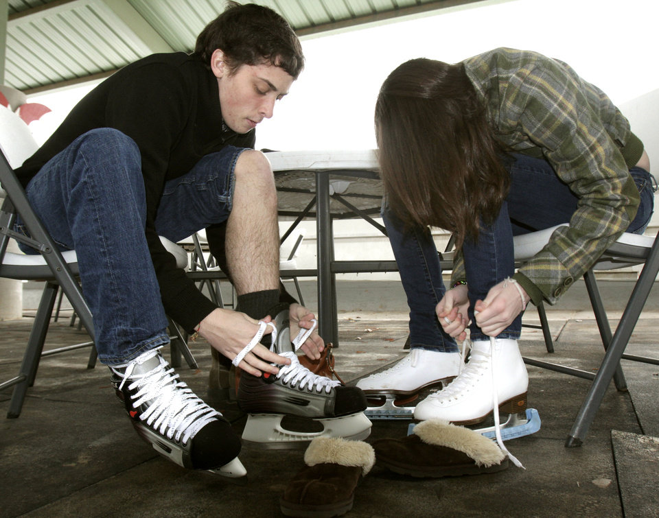 Cade Nelson and Tisha Stansberry lace up their skates as an outdoor skating rink opens at Edmond's Festival Market Place in Edmond, OK, Friday, Nov. 25, 2011. By Paul Hellstern, The Oklahoman