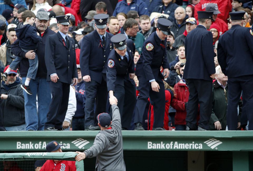 Photo - Firefighters shake hands with Boston Red Sox's Jonny Gomes after being honored between innings of the home opener baseball game at Fenway Park In Boston, Friday, April 4, 2014 between the Red Sox and the Milwaukee Brewers. (AP Photo/Elise Amendola)