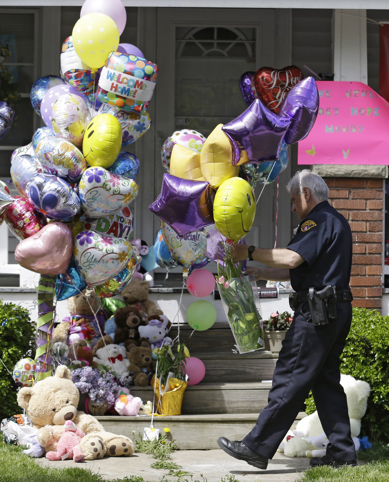 A Cleveland policeman carries balloons and flowers to the front porch of a home awaiting the arrival of Amanda Berry Wednesday, May 8, 2013, in Cleveland. Berry, 27, Michelle Knight, 32, and DeJesus,  had apparently been held captive in the house since their teens or early 20s, police said. (AP Photo/Tony Dejak)