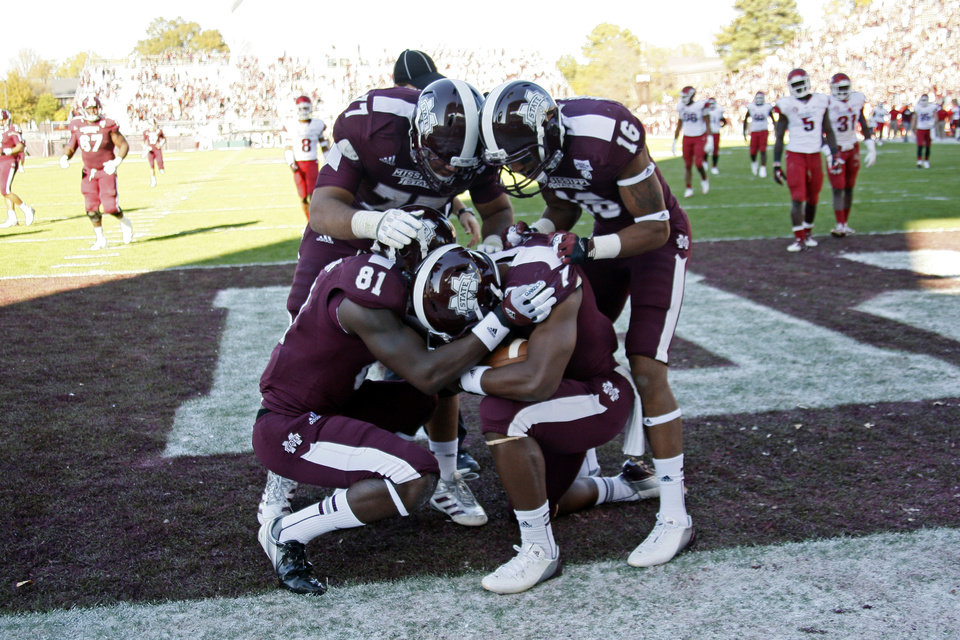 Photo -   Mississippi State players wide receivers Robert Johnson (81), Joe Morrow (16) and offensive linesman Charles Siddoway (77) join running back Nick Griffin (7) in a short prayer after Griffin scored on a 60-yard touchdown run against Arkansas during the fourth quarter of an NCAA college football game in Starkville, Miss., Saturday, Nov. 17, 2012. Mississippi State won 45-14. (AP Photo/Rogelio V. Solis)