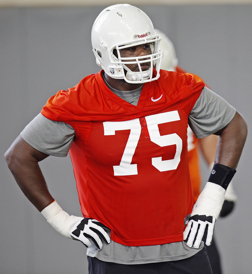 Photo - Oklahoma State offensive lineman Chris Grishby (75) stretches during the first team practice of the fall at the Sherman E. Smith Training Facility on the campus of Oklahoma State University in Stillwater on August 1, 2014. Photo by KT King, The Oklahoman