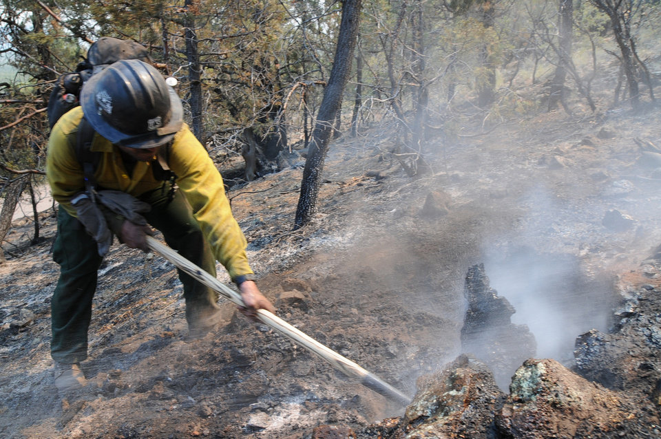 Photo -   This photo provided by the U.S. Forest Service shows a hotshot during burnout operations at the Gila National Forest blaze, Friday June 1, 2012. Fire officials said Friday, that the massive Gila Wilderness blaze is now nearly 217,000 acres. That's more than 25,000 acres larger than than the day before. (AP Photo/U.S. Forest Service Gila National Forest, Brandon Oberhardt)