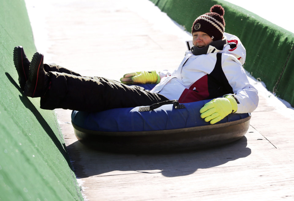 Photo - Dana Wallace slides at the Lifeshare Winterfest & Snow Tubing at the Chickasaw Bricktown Ballpark on Monday, Jan. 1, 2018 in Oklahoma City, Okla.  Photo by Steve Sisney, The Oklahoman