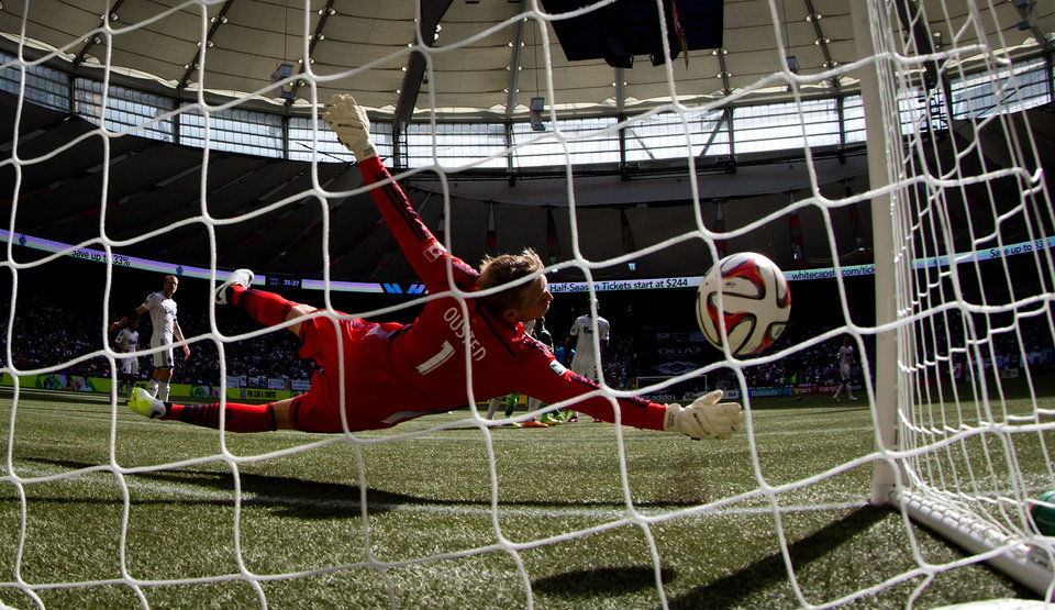 Photo - Vancouver Whitecaps' goalkeeper David Ousted, of Denmark, allows a goal to Seattle Sounders' Chad Barrett during the first half of an MLS soccer game in Vancouver, British Columbia, Saturday, May 24, 2014. (AP Photo/The Canadian Press, Darryl Dyck)