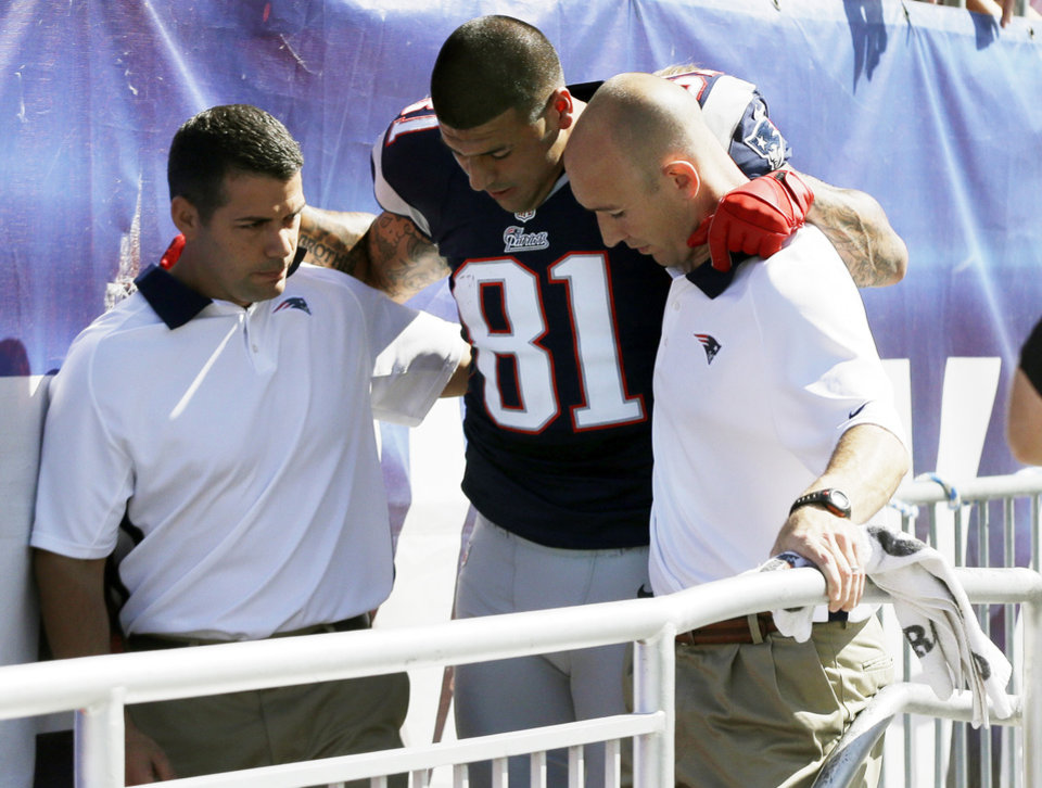 Photo -   New England Patriots tight end Aaron Hernandez is helped from the field in the first quarter of an NFL football game against the Arizona Cardinals, Sunday, Sept. 16, 2012, in Foxborough, Mass. (AP Photo/Elise Amendola)