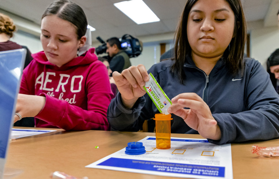 Photo - Students Margaret Mendz and Jennifer Hinojosa, from left, follow the directions to the drug disposal worksheet during the launch of an interactive prescription drug safety course designed for high school students at Capitol Hill High School in Oklahoma City, Okla. on Friday, Jan. 31, 2020. The safety program is launched by Attorney General Mike Hunter, executives from Walmart, EVERFI, and Oklahoma City Public Schools. [Chris Landsberger/The Oklahoman]