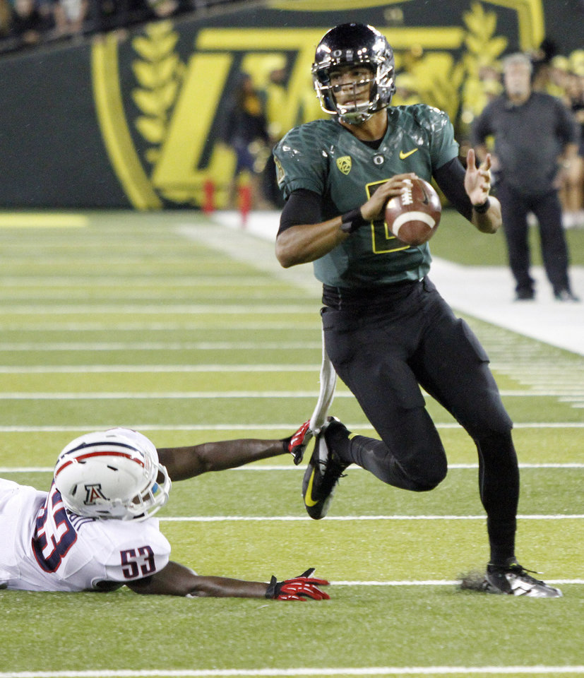 Photo -   Oregon quarterback Marcus Mariota, right, avoids Arizona defender Sir Thomas Jackson as he looks for a receiver during the second half of their NCAA college football game in Eugene, Ore., Saturday, Sept. 22, 2012. Mariota threw for 260 yards and two touchdowns as Oregon won 49-0.(AP Photo/Don Ryan)