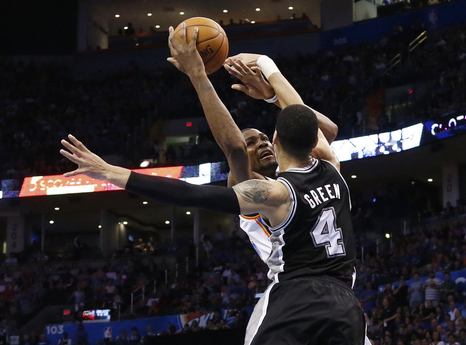 Photo - Oklahoma City Thunder forward Kevin Durant (35) is fouled by San Antonio Spurs guard Danny Green (4) on a shot during the second quarter of an NBA basketball game in Oklahoma City, Thursday, April 3, 2014. (AP Photo/Sue Ogrocki)